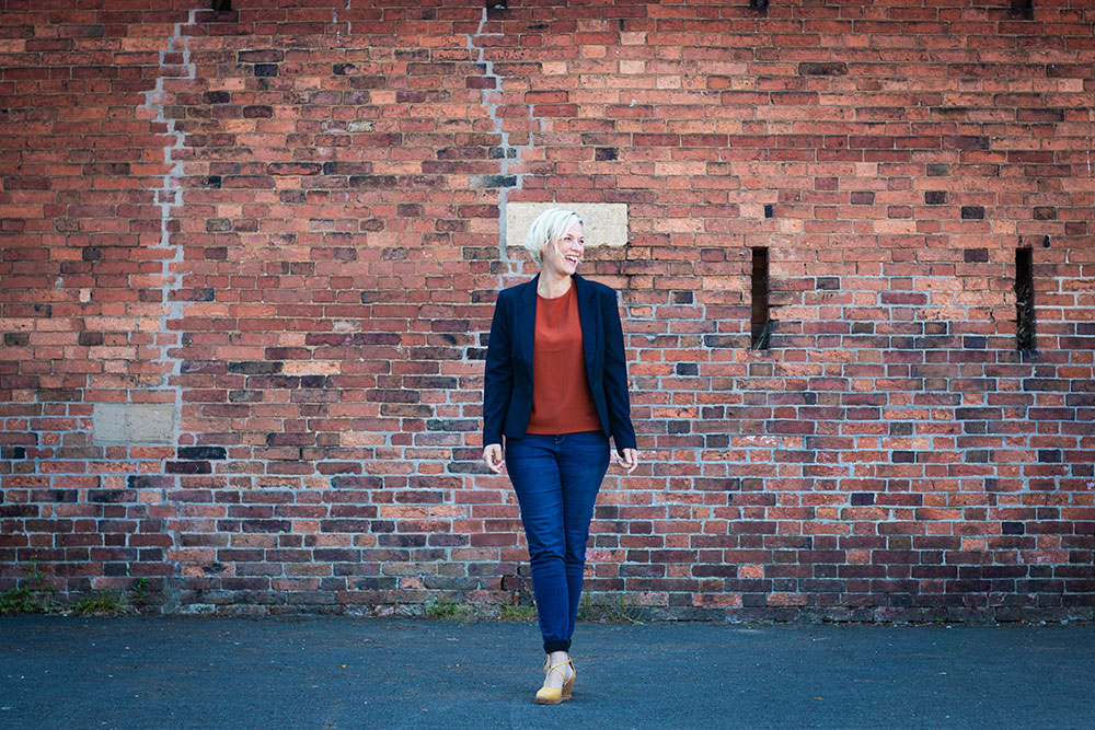 Life Coach stood laughing in front of rustic brick wall